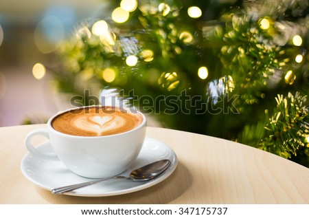 Photo of beautiful Christmas light festive, white coffee cup on the wooden table on bokeh background - stock photo