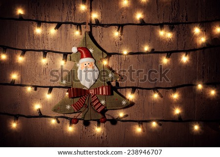 Photo of beautiful Christmastime ornament, decorative Christmas tree hanging on the door decorated with glowing garland at home, wooden xmas toy on dark brown grunge background, happy New Year - stock photo