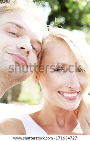 Photo of beautiful happy couple looking at camera and smiling. Summer day. - stock photo