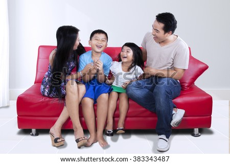 Photo of beautiful happy family sitting on the couch while having fun and laughing together at home - stock photo