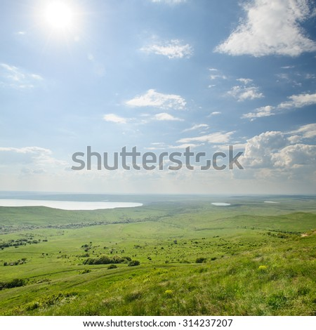 Photo of beautiful landscape with grassy and land lake under sunny skies - stock photo