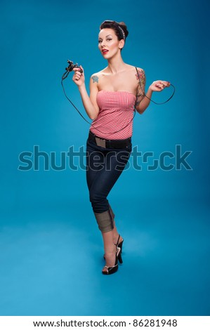 Photo of beautiful pin-up girl with tattoos and tattoo machine tattoing herself and looking at the camera - stock photo