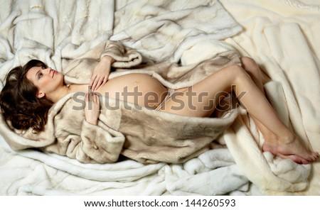Photo of beautiful pregnant woman in luxurious fur coat - stock photo