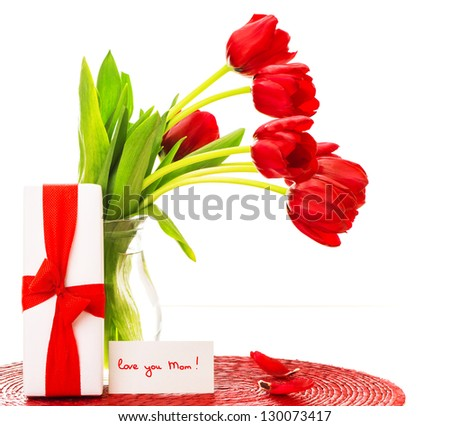 Photo of beautiful red tulips bouquet in vase, white giftbox with ribbon, greeting card, love you mom, happy mothers day, flowers bunch as present, romantic still life, merry holiday, love concept - stock photo