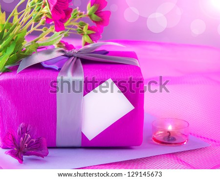 Photo of beautiful romantic still life, pink giftbox with violet silk ribbon, fresh flowers bouquet, romantic candle, greeting paper card with copy space, happy mothers day, present for birthday - stock photo