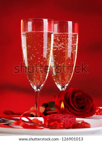 Photo of beautiful Valentine day dinner still life, two glasses for champagne, alcohol beverage, romantic drink, sparkling wine, red rose and candle, festive table setting, love concept - stock photo