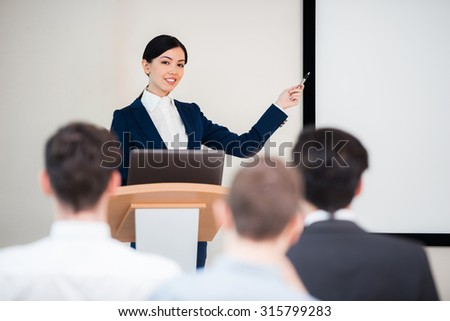 Photo of beautiful young business woman making presentation with whiteboard on seminar or meeting to business people - stock photo