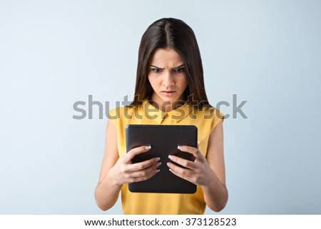 Photo of beautiful young business woman standing near gray background. Angry woman with yellow shirt using tablet computer - stock photo