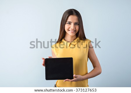 Photo of beautiful young business woman standing near gray background. Smiling woman with yellow shirt showing tablet computer and looking at camera - stock photo