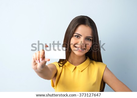 Photo of beautiful young business woman standing near gray background. Woman with yellow shirt looking at camera, smiling and showing visit card - stock photo