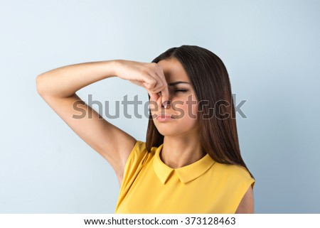 Photo of beautiful young business woman standing near gray background. Woman with yellow shirt covering her nose from smell - stock photo