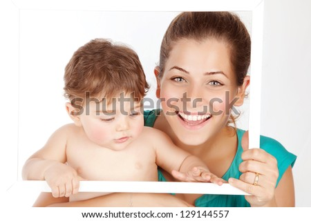 Photo of beautiful young mother with cute baby boy holding white frame, pretty woman carrying little son isolated on white background, smiling faces, healthy lifestyle, happy motherhood concept - stock photo