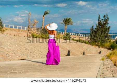 Photo of  beautiful young woman in a hat at sea resort - stock photo