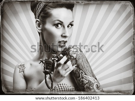 Photo of beautifull pin-up girl with tattoos and tattoo machine tattoing herself and looking at the camera - stock photo