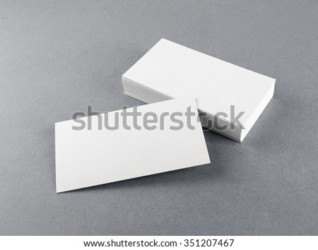 Photo of blank business cards with soft shadows on gray background. For design presentations and portfolios. Mock-up for branding identity. - stock photo