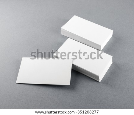 Photo of blank business cards with soft shadows on gray background. Template for branding identity. - stock photo