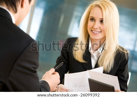 Photo of blond businesswoman looking at her colleague while he explaining his idea - stock photo