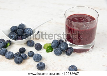 Photo of blueberries and smoothie in a glass on white wooden board - stock photo