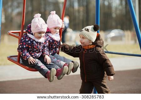 photo of boy rolls girls on the swings - stock photo