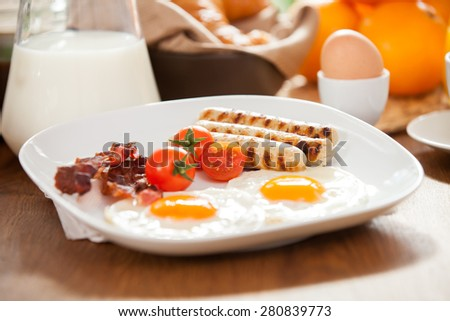 Photo of breakfast table with a plate of delicious english breakfast - stock photo