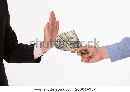 Photo of bribetaking. Man in blue-coloured shirt giving money to man in brown-coloured business suit. - stock photo