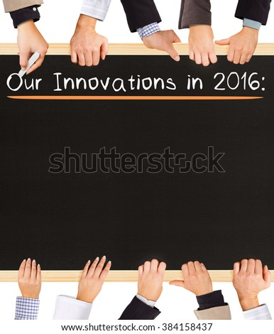 Photo of business hands holding blackboard and writing Our Innovations in 2016 - stock photo