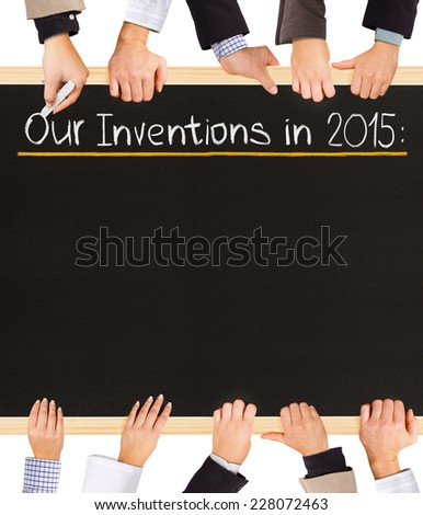 Photo of business hands holding blackboard and writing Our Inventions for 2015 - stock photo