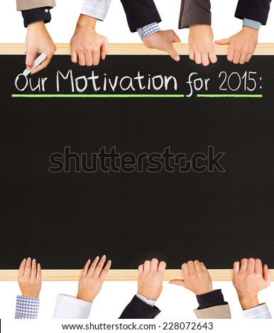 Photo of business hands holding blackboard and writing Our Motivation for 2015 - stock photo