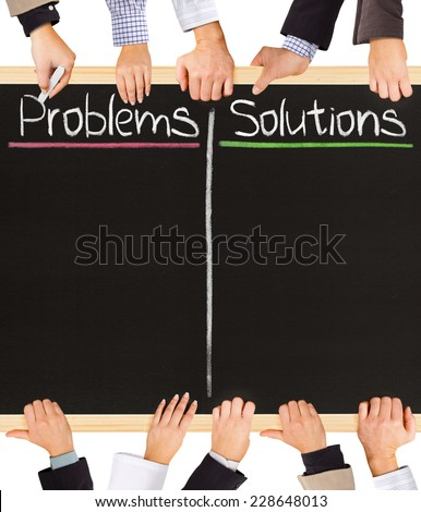 Photo of business hands holding blackboard and writing Problems and Solutions - stock photo
