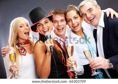 Photo of businesspeople with flutes of champagne singing at Christmas party - stock photo