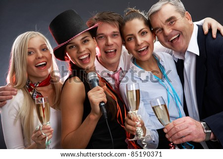 Photo of businesspeople with flutes of sparkling champagne singing Christmas songs - stock photo