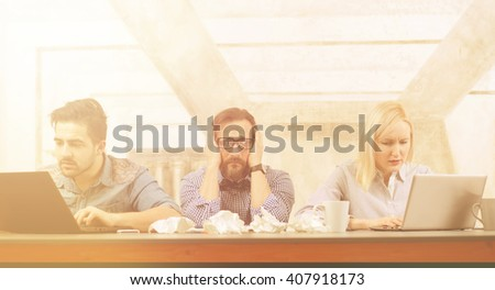 Photo of busy business people working upon their own projects in company. Man in middle closing his ears while his colleagues working on laptop computers. - stock photo