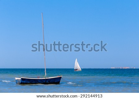 Photo of calm blue sea on a sunny day, where the foreground is a beautiful small sailboat, and in the background a sailboat with sails.It is seen in distant city. - stock photo