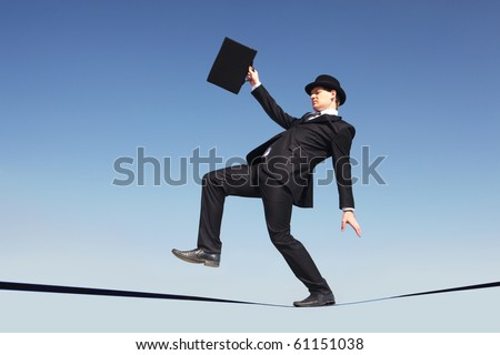 Photo of careful businessman standing on ribbon or rope running risk of falling down - stock photo