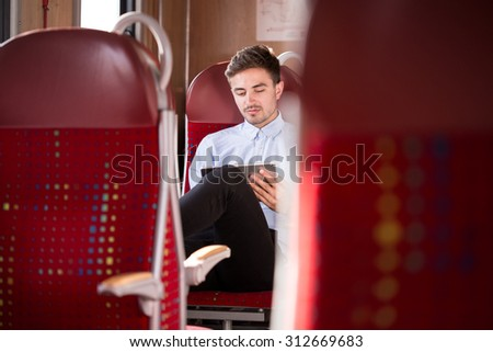 Photo of casual businessman travelling by bus instead of car - stock photo