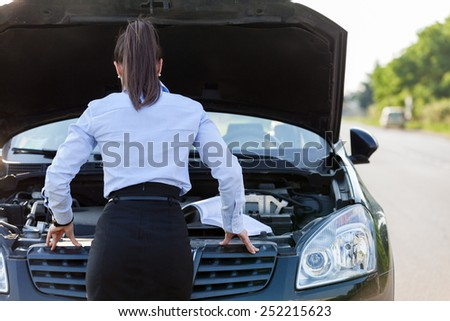 Photo of caucasian businesswoman looking inside the car hood - stock photo