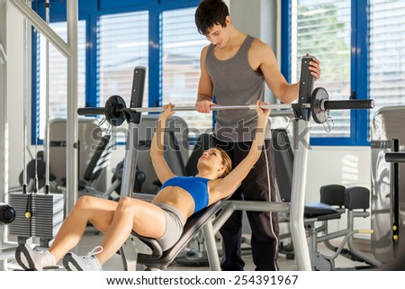 Photo of caucasian woman doing dumbbell exercise in gym - stock photo