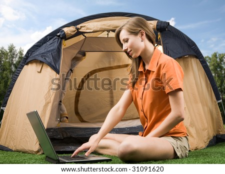 Photo of charming female sitting on green grass and typing with tent near by - stock photo