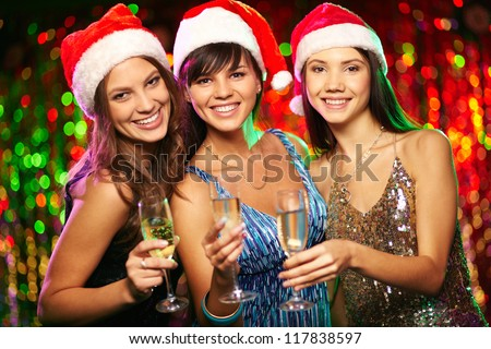 Photo of cheerful girls looking at camera with smiles while enjoying Christmas party - stock photo