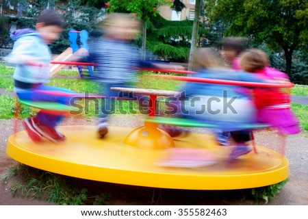 Photo of children having fun at colorful carousel spinning round fast - stock photo