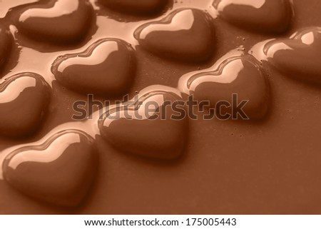 Photo of chocolate hearts covered in creamy milk chocolate shot at an angle with copy space for your own message. - stock photo