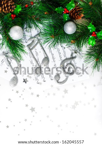 Photo of Christmas tree border, silver treble clef, festive melody on the notes page, musical sound, traditional Christmastime song, green pine tree branch decorated with cones, red berry and baubles - stock photo