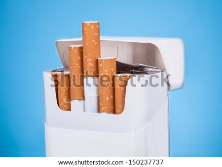 Photo Of Cigarettes In Pack Over Blue Background - stock photo