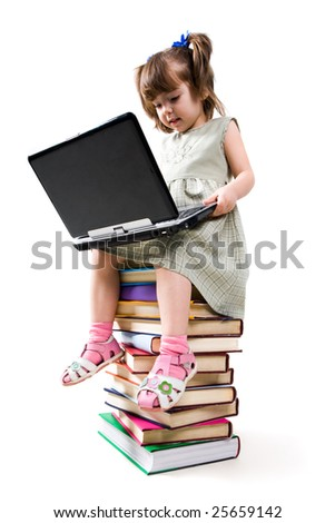 Photo of clever child with laptop on her knees looking at its keypad - stock photo