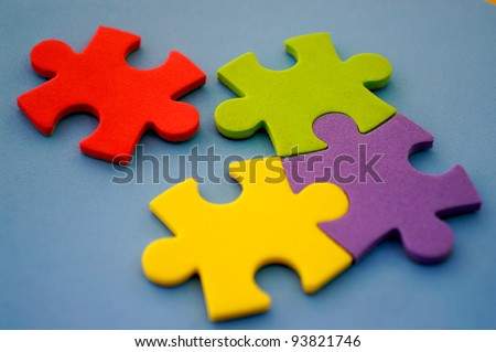 Photo of colorful puzzles with red piece separated and focus on red. - stock photo