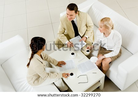 Photo of company of successful partners discussing contract at meeting - stock photo