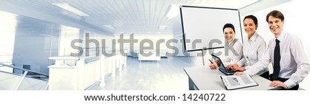 Photo of confident business team sitting at desk and looking at camera with smiles - stock photo