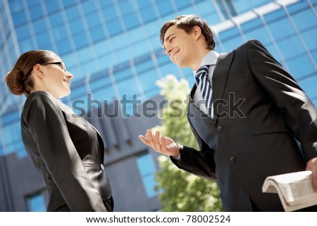 Photo of confident businessman looking at associate while communicating with her - stock photo