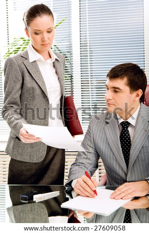 Photo of confident leader looking at documents being shown by his secretary - stock photo