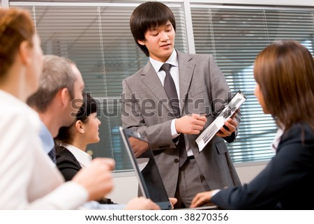 Photo of confident leader pointing at paper with diagrams during meeting - stock photo